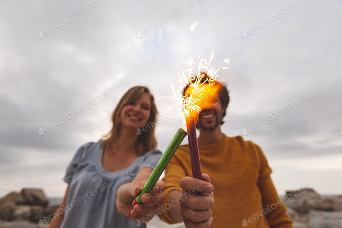 Young Caucasian couple playing with fire cracker while standing at beach.
