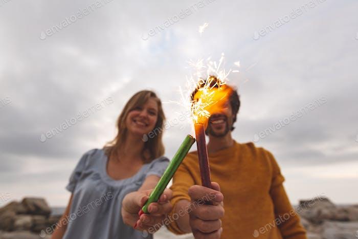 Junges kaukasisches Paar, das mit Feuer Cracker spielt, während am Strand steht.