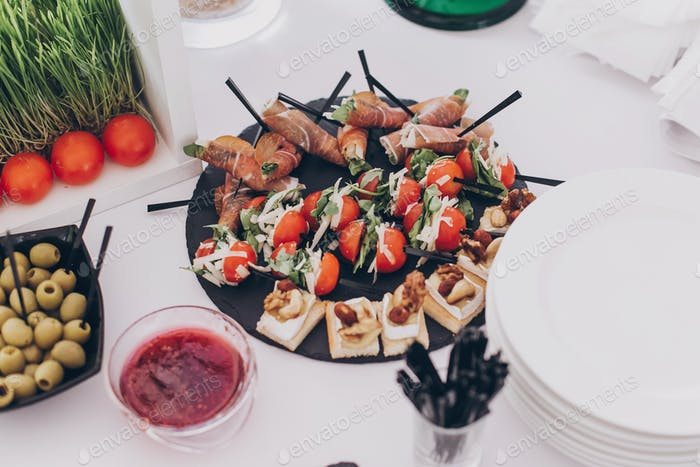 Delicious appetizer and canape on table at wedding reception in restaurant