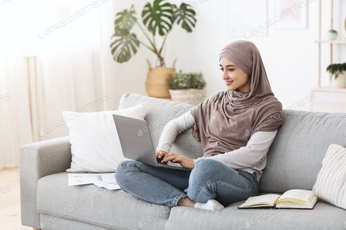 Remote Business. Happy Arabic Businesswoman Working With Laptop And Documents At Home