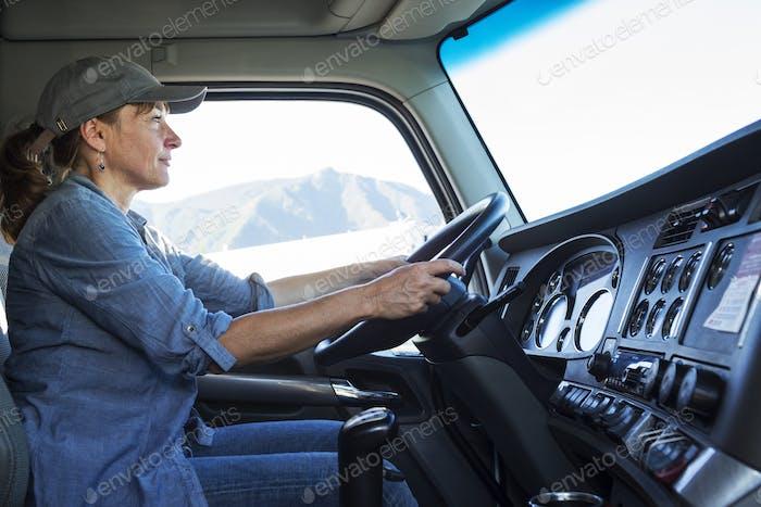 Kaukasische Frau LKW-Fahrer in der Kabine ihres kommerziell LKW an einem LKW-Stopp