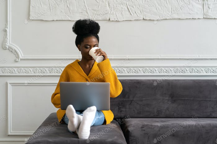 Afro millennial woman sitting on couch, working online on laptop, watching webinar, drinking coffee