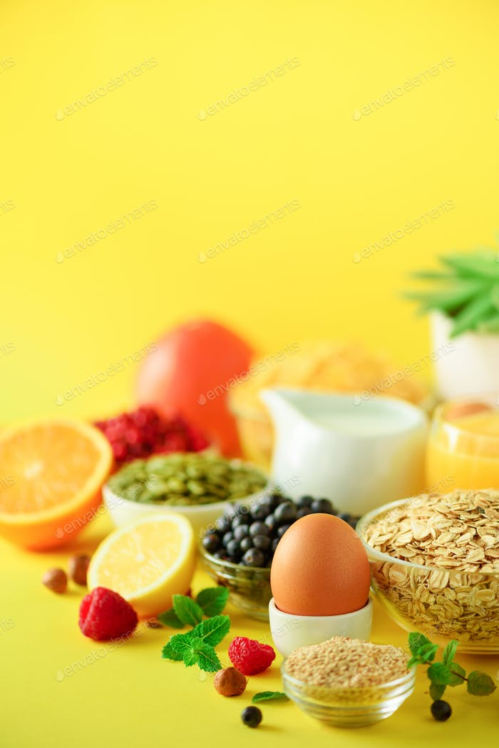 Breakfast served with soft boiled egg, oat flakes, nuts, fruits, berries, milk, yogurt, orange