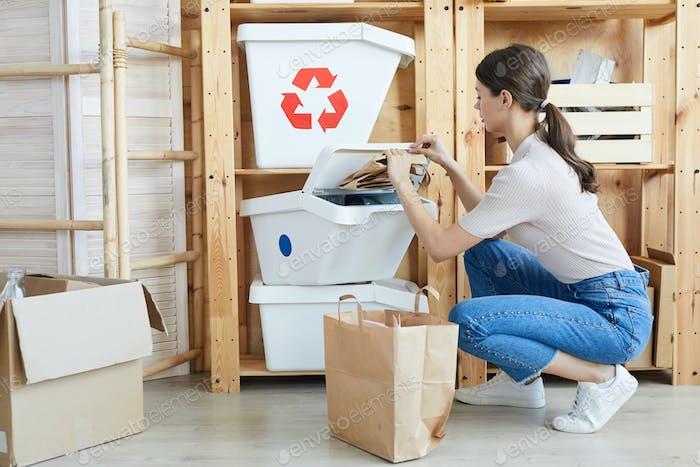 Frau, die Papier von anderen Abfällen trennt