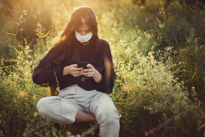 Modische junge Frau mit Smartphone und tragen Schutzmaske im Freien
