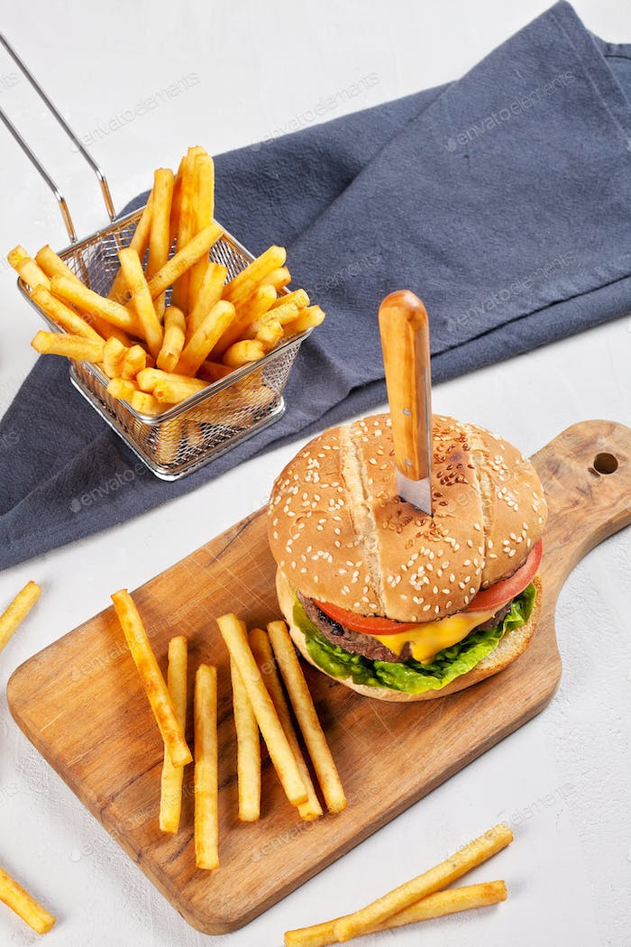 Fresh tasty burger with cheese, tomato and salad with french fries