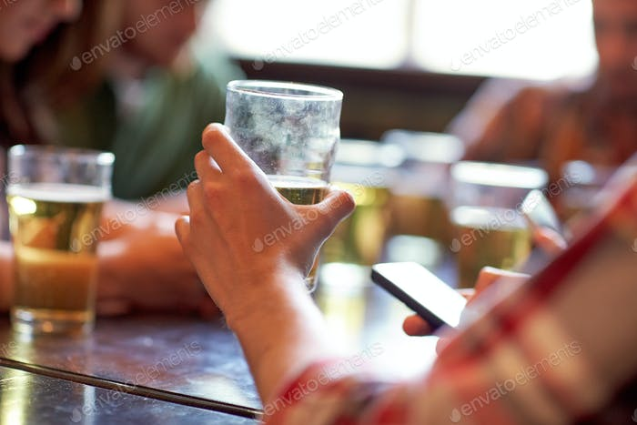 man with beer and smartphones at bar or pub