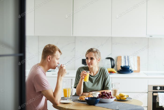 Young woman and her husband drinking orange juice by breakfast