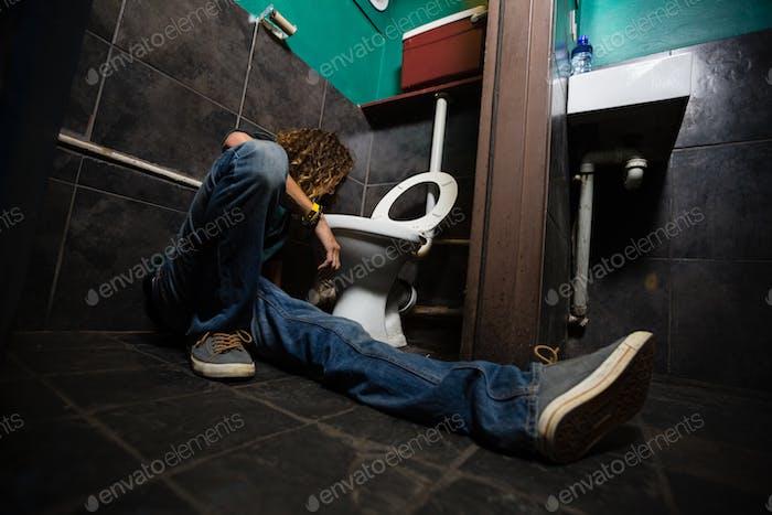 Man vomiting on toilet bowl