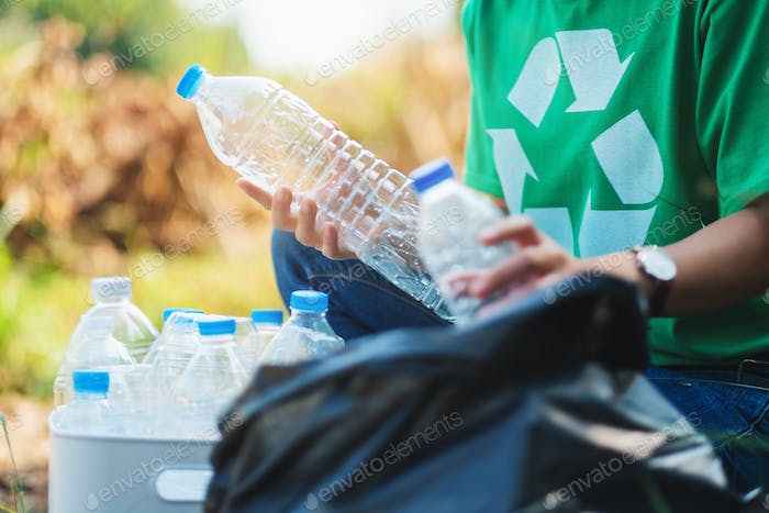 A woman picking up garbage plastic bottles into a box and bag for recycling concept