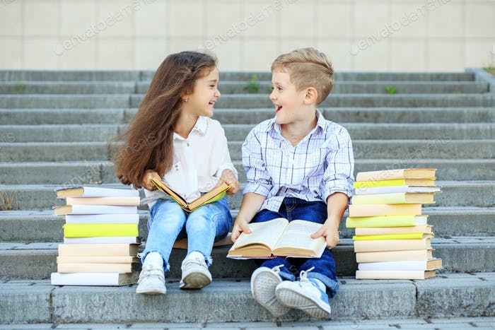 Two students read books and communicate. The concept is back to school, education, reading