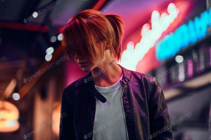 Stylish redhead girl standing in the night on the street. Illuminated signboards, neon, lights.