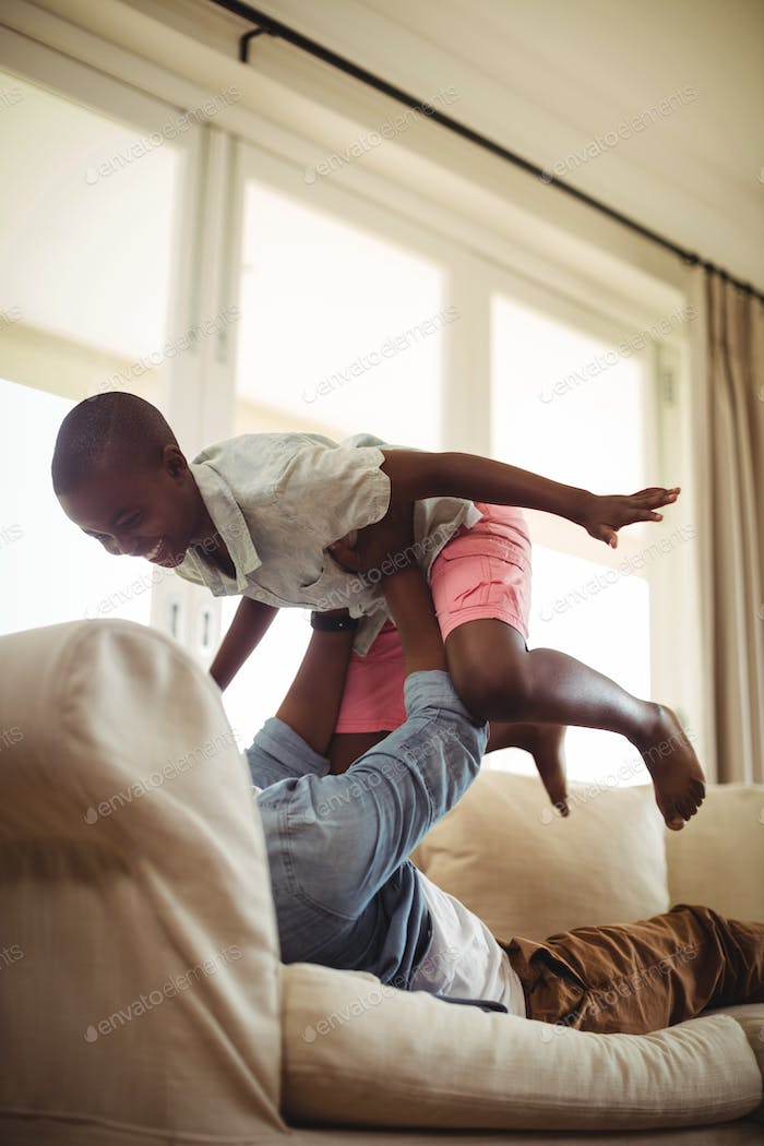 Father playing with son on sofa in living room