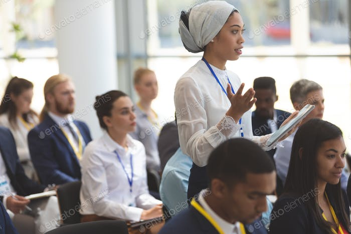 Young businesswoman with headscarf asking question during seminar in office building