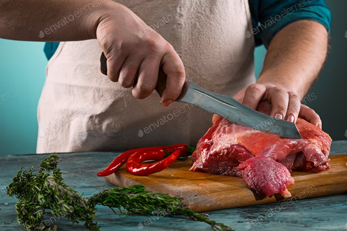 Butcher cutting pork meat on kitchen