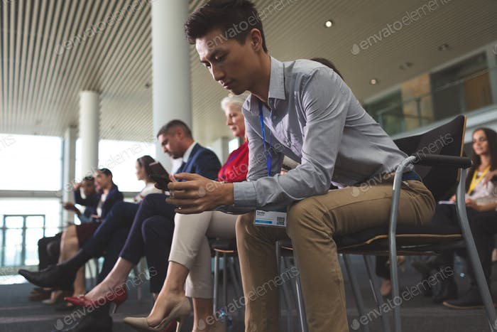 Young Asian businessman using mobile phone during business seminar