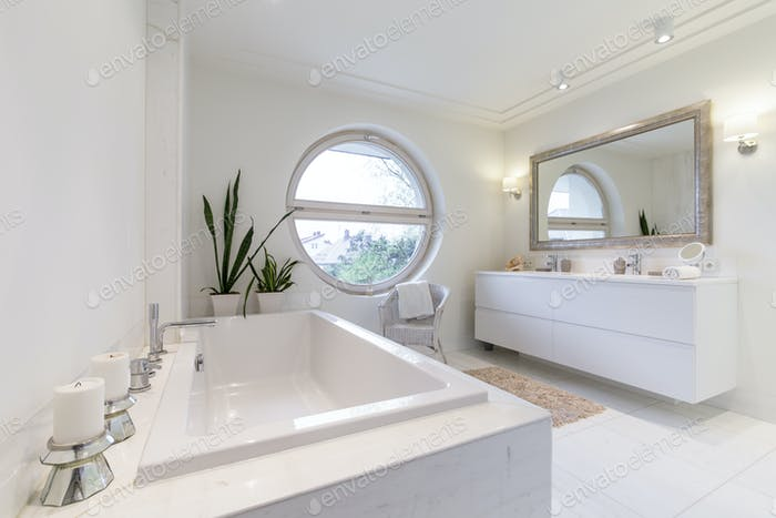 Minimalist white bathroom with a circulal window