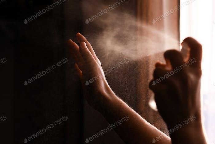 Person, die antiseptisches Spray auf die Hände verwendet, um Coronavirus oder Grippe-Krankheit zu verhindern
