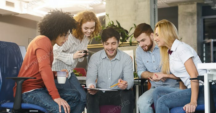 Group of young coworkers discussing new marketing strategy in office