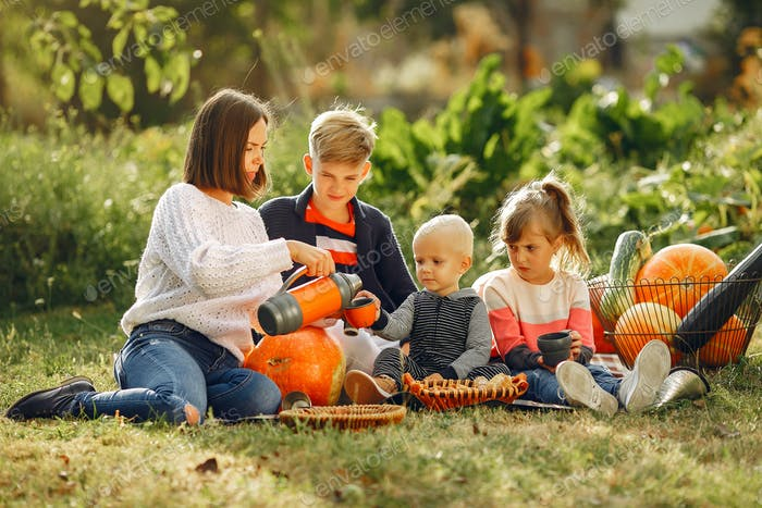 Big family sitting on a garden near many pumpkins