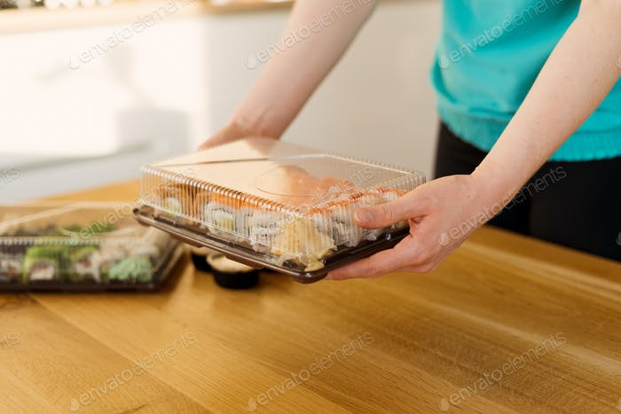 Woman holding box of sushi for delivery