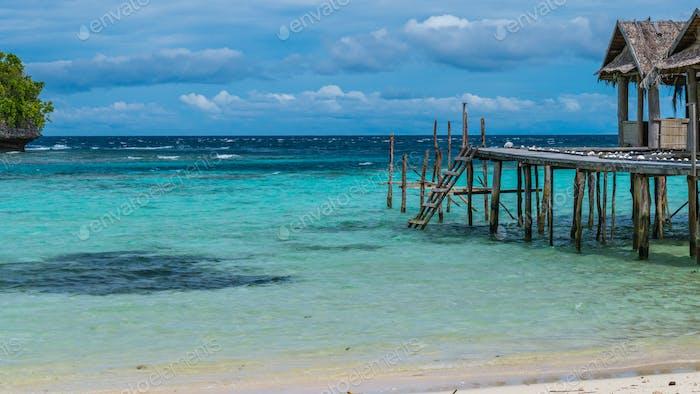 Hermosa Lagoone Azul con algunas cabañas de bambú, Kordiris Homestay, Palmtree en frente, Isla Gam, Oeste
