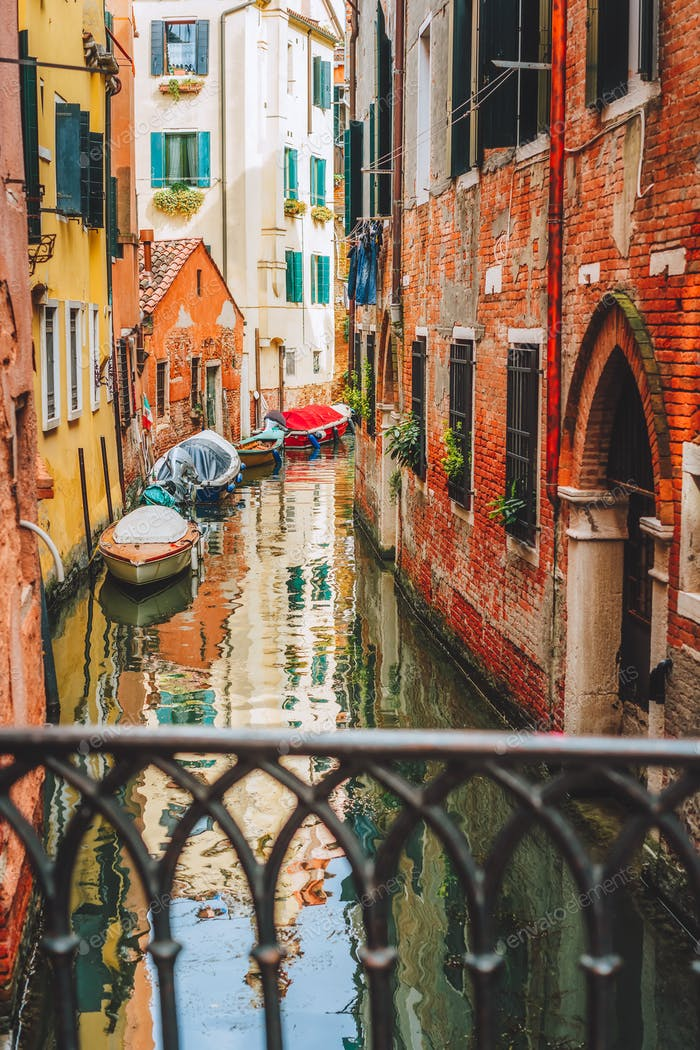 Venice, Italy. Narrow channel street and colored houses with local boats in Venezia
