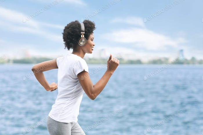 Positive Black Girl Running Outside Along River Embankment