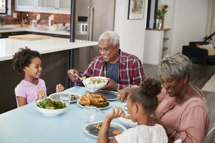 Grandparents Enjoying Meal At Home With Granddaughters