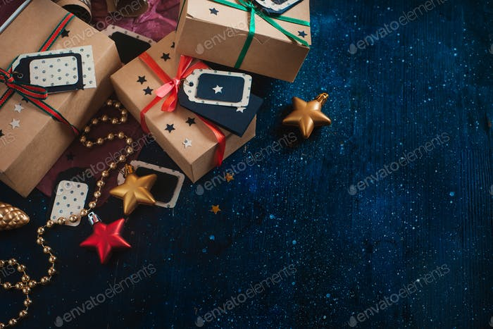 Decorations and wrapped presents concept. Christmas celebration dark flat lay with craft paper boxes