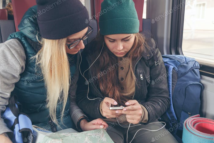 Couple of female friends looking at the smartphone while on the train