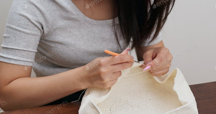 Woman is crocheting with thread at home