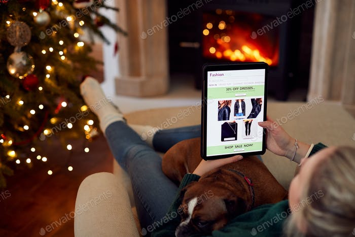Woman At Home With Pet Dog Using Digital Tablet To Shop For Clothes Online At Christmas