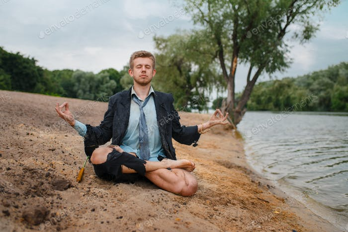 Office worker sitting on the beach in yoga pose