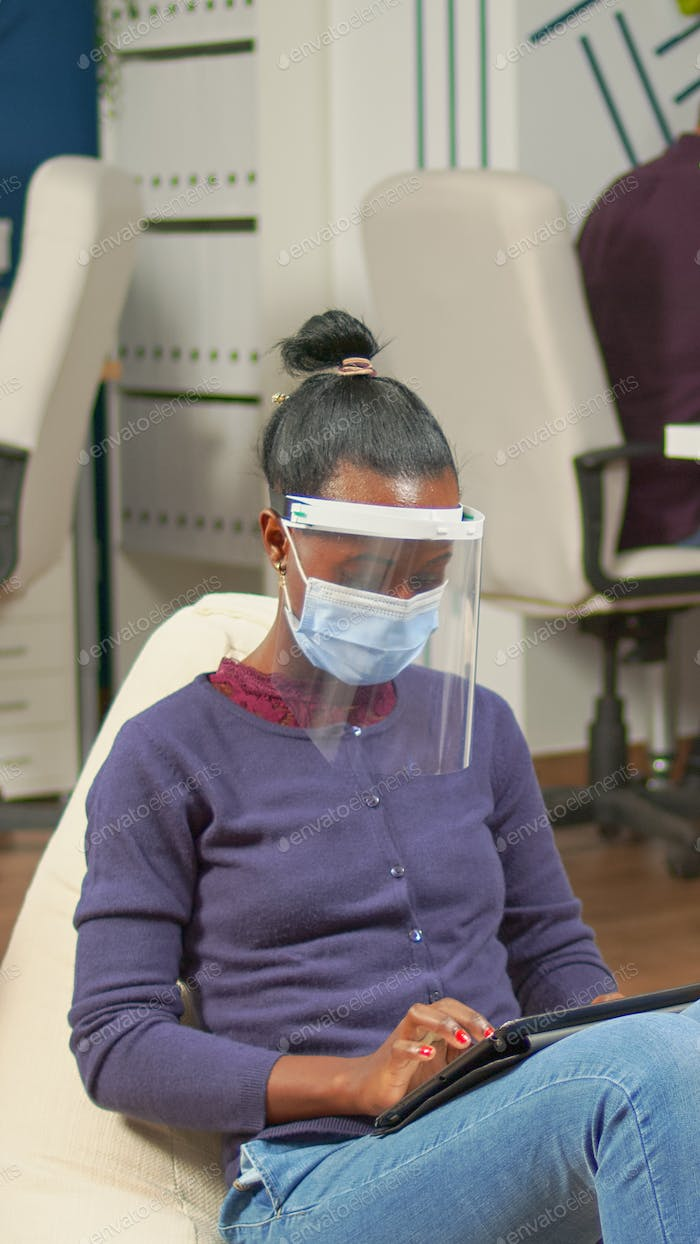 Black businesswoman with mask against covid19 working on armchair