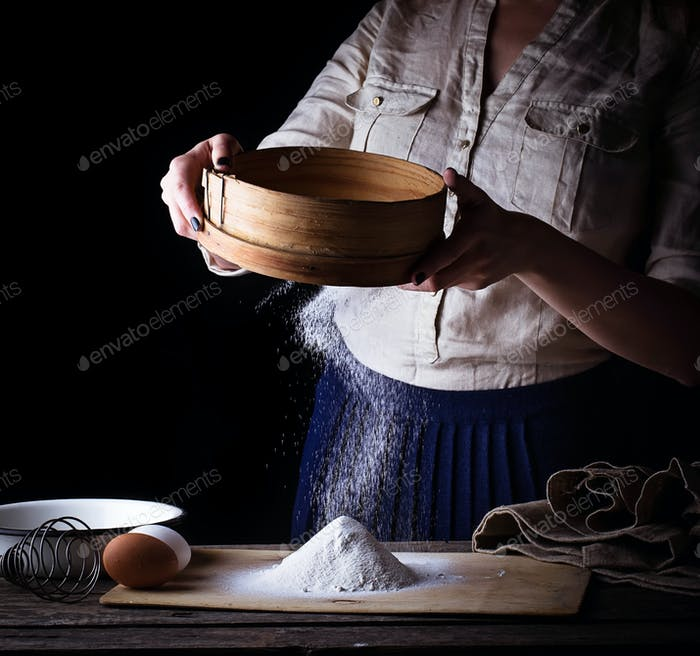Woman sifting flour through  sieve