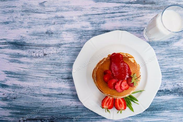Pfannkuchen mit frischer Erdbeere und Minze auf weißem Teller auf rosa Holzhintergrund im Garten