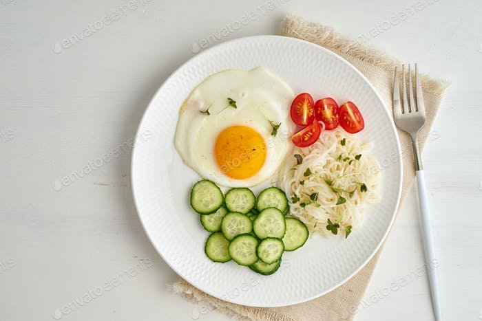 Healthy breakfast - fried egg with cherry tomatoes and cucumber