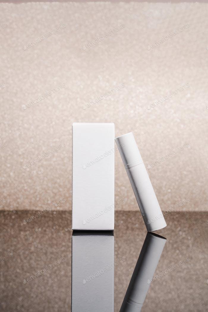Weiße Kosmetik-Tube und Box auf Roségold-Glitzer