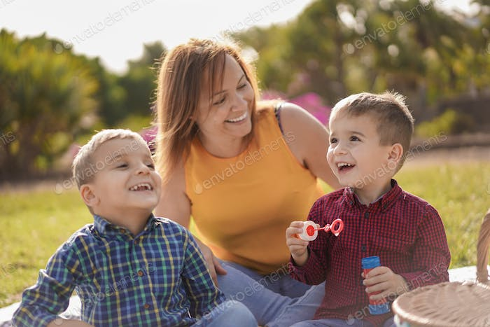 Happy mother with twin sons laughing - Young mother enjoy the day with her children in a nature park