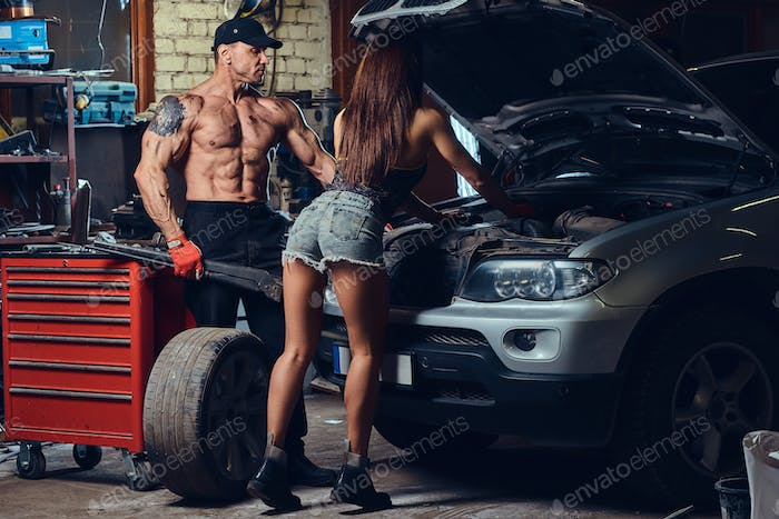 A couple in a garage.