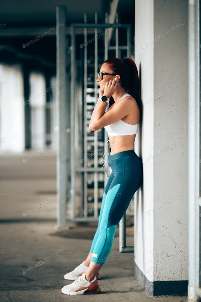 Portrait of attractive woman listening to music and training. Modern fitness concept