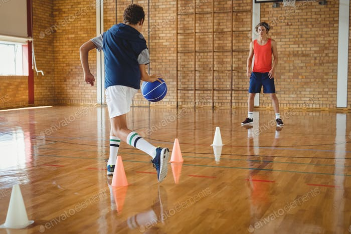 High school boys practicing football using cones for dribbling drill