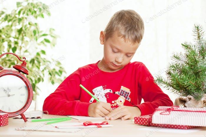 Little boy writes a letter to Santa Claus