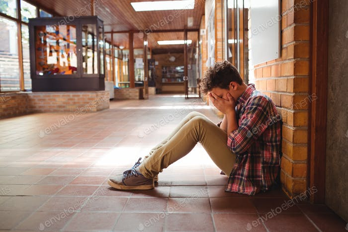 Sad schoolboy sitting alone in corridor