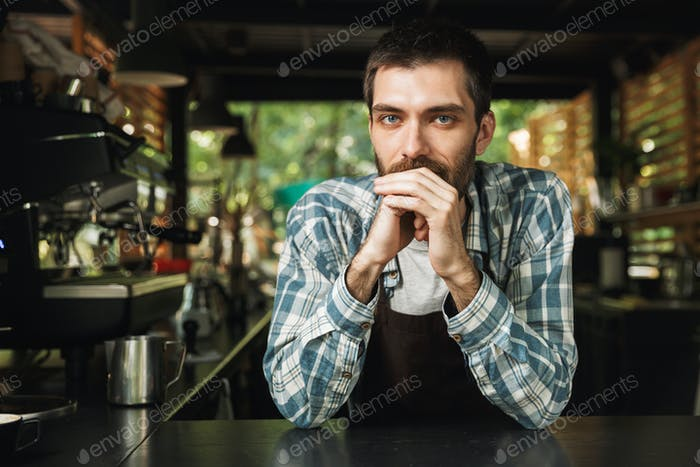 Portrait of handsome barista guy smiling at camera while working