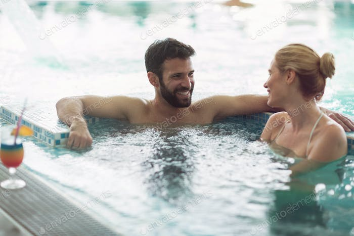 Cheerful happy couple relaxing in swimming pool