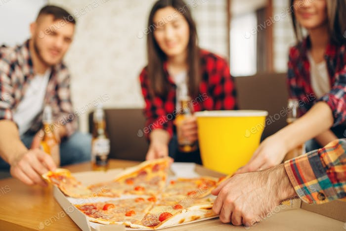 Friends drinks beer with pizza at the house party