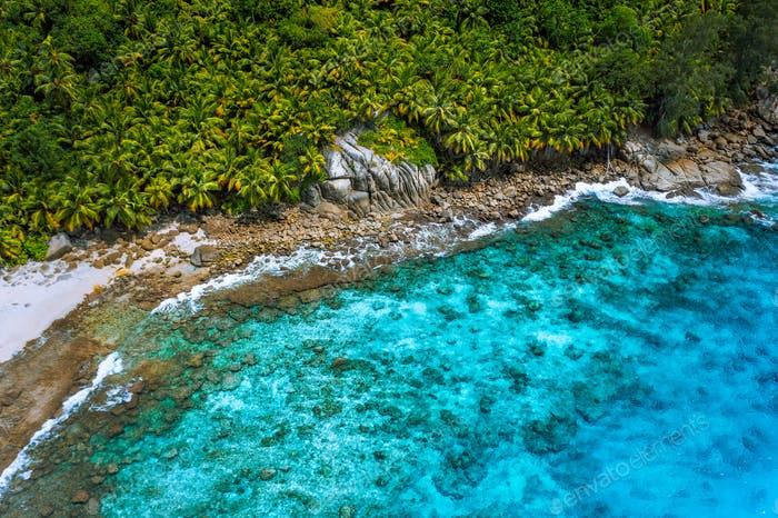 Aerial view of wild secluded lonely beach with rough granite rocks, white sand, palm trees in a