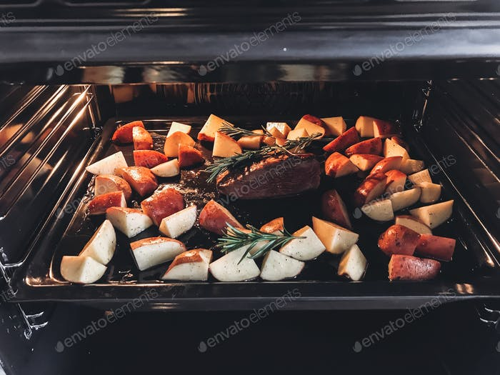 Delicious roasted steak with potatoes and rosemary branches on tray in oven